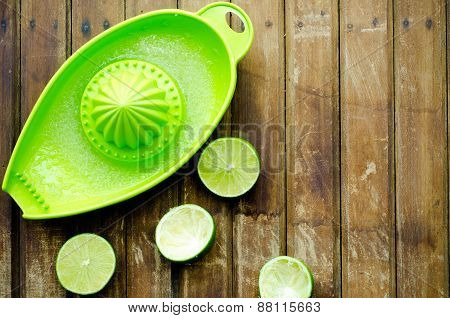 Green Limes With Green Manual Juicer On The Table