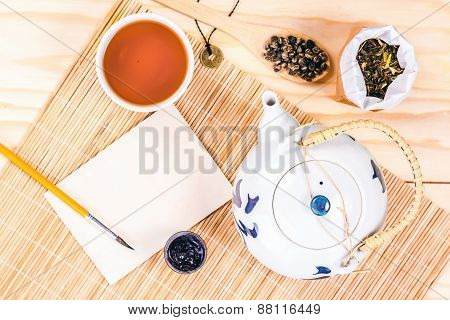 blank card and chinese set tea on wooden table, top view