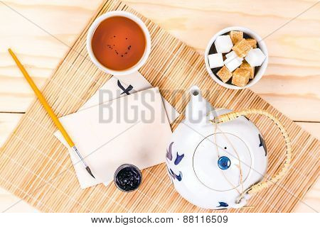 chinese set of tea and blank card on wooden table, view from above