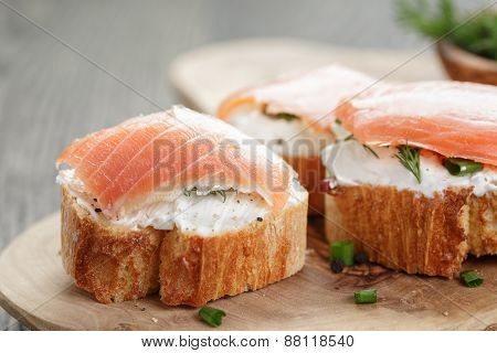 baguette slices with smoked salmon and cheese cream on wooden table