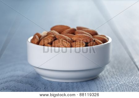 roasted almonds in white bowl on wooden table