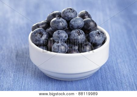 heap of fresh washed blueberries in white bowl on blue wood table