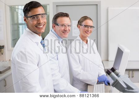 Smiling scientists looking at camera in laboratory
