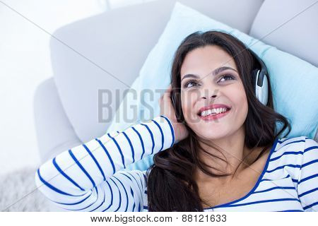 Smiling beautiful brunette relaxing on the couch and listening music in the living room