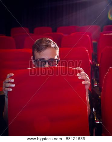 Young man watching a scary 3d film at the cinema