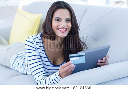 Smiling beautiful brunette doing online shopping on the couch in the living room