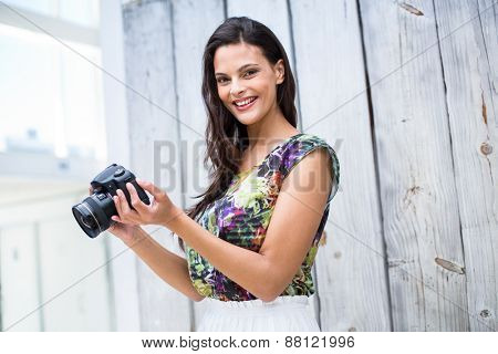 Smiling beautiful brunette taking pictures on wooden plank background