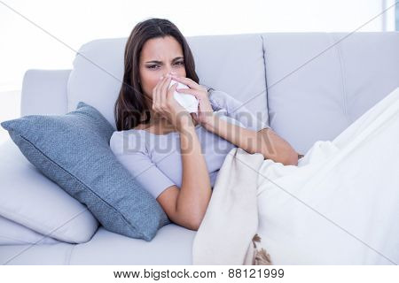 Sick brunette lying on the couch and blowing her nose in the living room