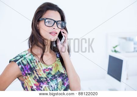 Smiling beautiful brunette standing in front of her computer and speaking on the phone