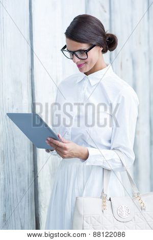 Pretty woman using her tablet pc in front of wooden grey planks
