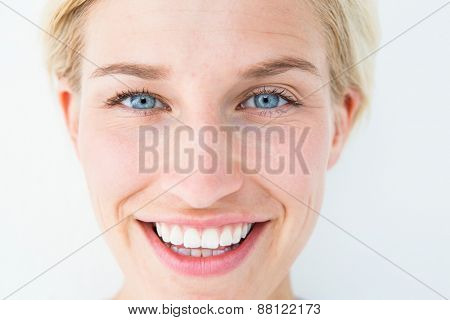 Happy blonde smiling at camera on white background