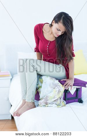 Woman sitting down on top of her suitcase at home