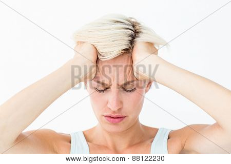 Blonde woman suffering from headache holding her head on white background