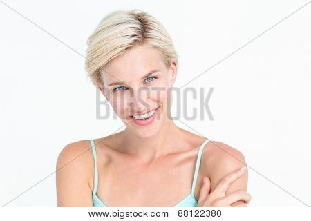 Beautiful blonde woman smiling at camera on white background