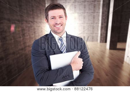 Businessman holding his laptop tightly against abstract room