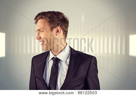 Young handsome businessman looking away against white curved room with light