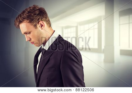 Young handsome businessman looking down against white room with windows