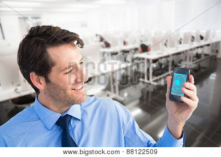 Smiling businessman showing smartphone to camera against empty computer room