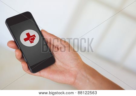 Womans hand holding black smartphone against heart and cross