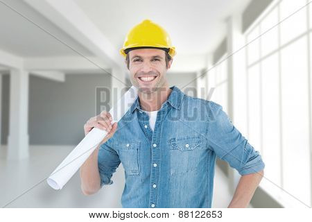 Confident architect holding rolled blueprint against modern white room with window
