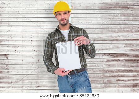smiling manual worker holding clipboard against digitally generated grey wooden planks