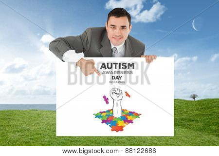 Businessman pointing at sign under him against field and sky