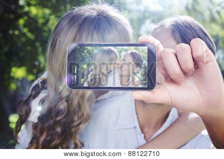 Hand holding smartphone showing against affectionate couple relaxing on park bench together