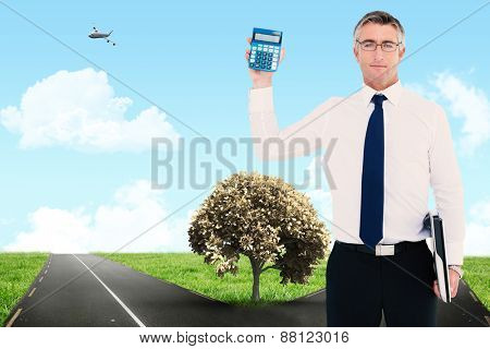 Businessman showing calculator while holding his laptop against road leading out to the horizon