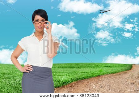 Thoughtful businesswoman against road leading out to the horizon