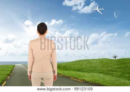 Asian businesswoman against road leading out to the horizon