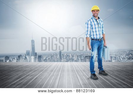 Manual worker with hammer and toolbox against room with large window looking on city