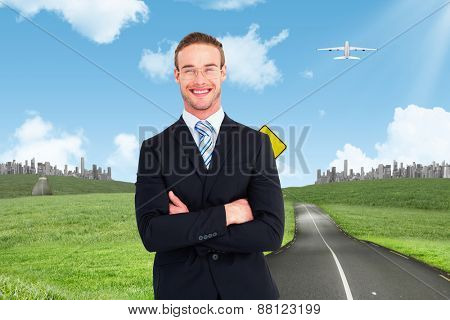 Smiling businessman in suit with arms crossed against road leading out to the horizon