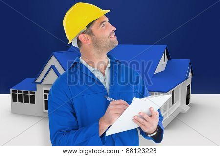 Male supervisor looking up while writing on clipboard against blue house standing with energy rating