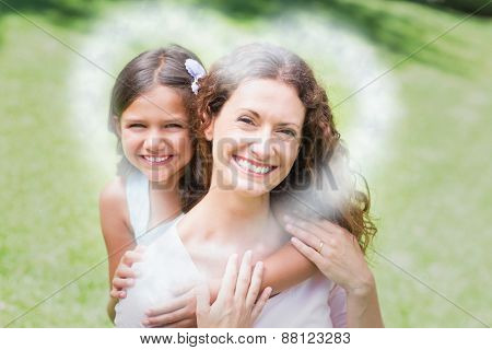 Cloud in shape of heart against happy mother and daughter hugging