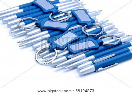 Silver-blue Metal Pens And Keychains Isolated On White.