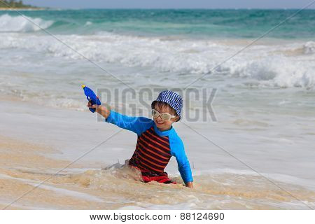 little boy playing with water gun on the beach