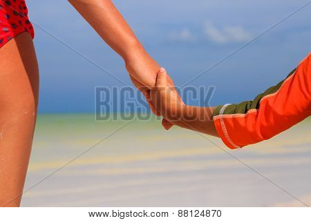 mother and child holding hands on sea beach