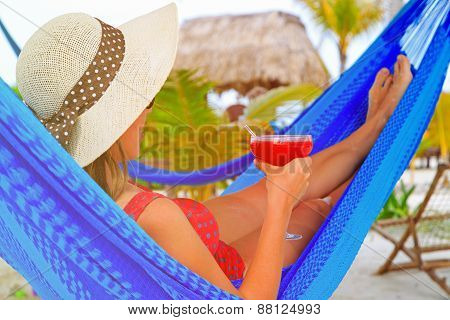 woman with cocktail relaxed in hammock on the beach
