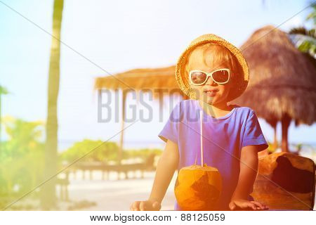 little boy drinking coconut cocktail on the beach