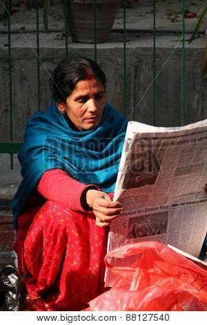 KATHMANDU, NEPAL-DECEMBER, 2009 - An unidentified nepalese woman reading newspaper in the morning