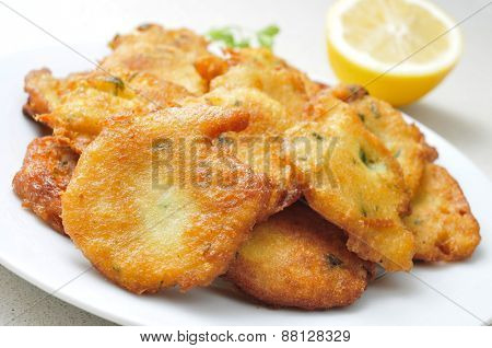 closeup of a plate with a pile of appetizing tortas de bacalao, spanish cod cakes, on a white surface