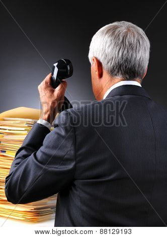 Mature businessman seen from behind as he answers the telephone facing a pile of work on his desk. Vertical format on a light to dark gray background.