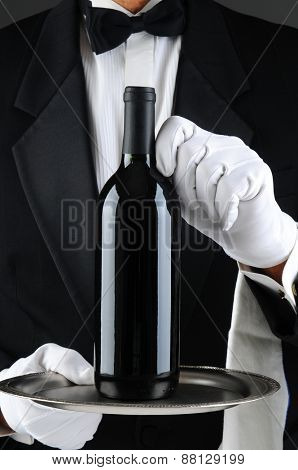 Closeup of a waiter wearing a tuxedo and white gloves holding a wine bottle on a serving tray. Vertical format. The man is unrecognizable.