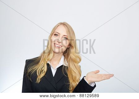 young blonde woman in a suit, with her hand outstretched.