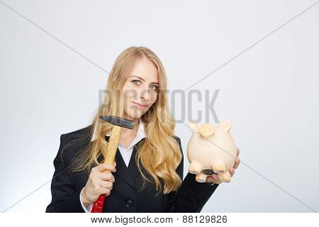 Serious businesswoman holding a piggy-bank and hammer