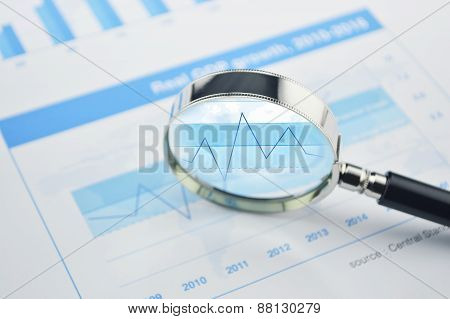Magnifying Glass Over Financial Chart And Graph Business