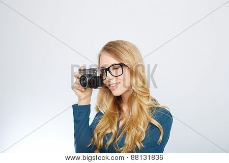 young blond woman with a vintage camera