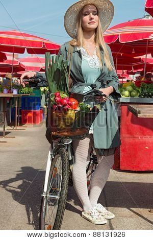 Attractive blonde woman with straw hat and bike on Marketplace.