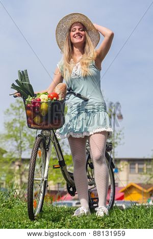 Attractive blonde woman with straw hat posing next to bike with basket full of groceries.