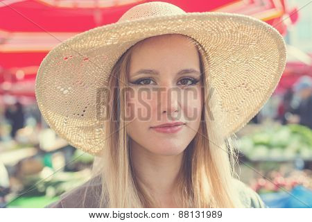 Portrait of attractive blonde girl with straw hat on Marketplace. Post processed with vintage filter.